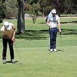 Chantha putts while Corey looks on